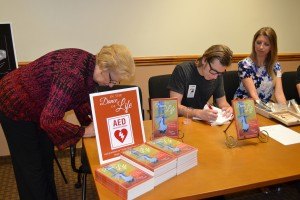 Suzanne & Paul Henry signing books as Lauren looks on website